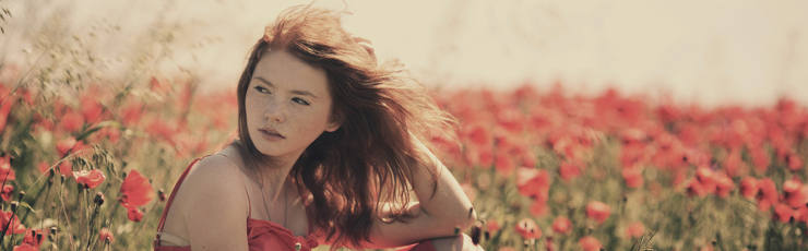 young red haired beautiful girl in poppy field